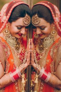 Image That Resembles A Bride Who Poses in Her Wedding Photoshoot infront of the mirror with a Beautiful Smile on her face