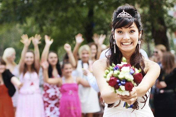 A Smiling Bride Getting Ready To Toss Her Flower Bouqet To Know Which Bridesmaid Will Get Married Next.